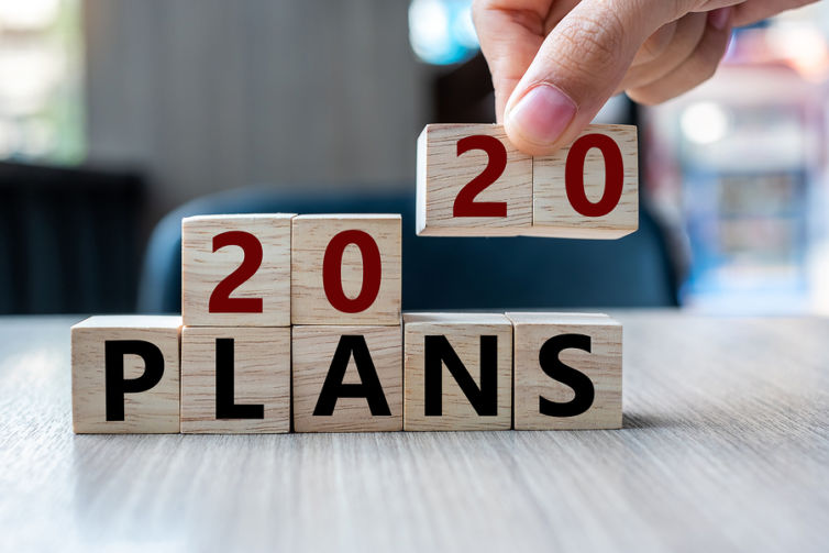 Business Man Hand Holding Wooden Cube With 2020 Plans Word On Ta